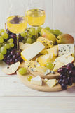 Cheese plate served with wine, fresh grapes and pears Royalty Free Stock Photography