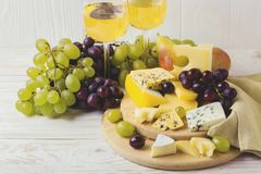 Cheese plate served with wine, fresh grapes and pears Royalty Free Stock Image