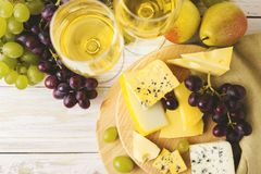 Cheese plate served with wine, fresh grapes and pears Stock Photos