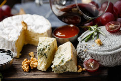 Cheese plate served with wine, jam and honey Royalty Free Stock Photos
