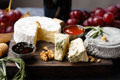 Cheese plate served with wine, jam and honey Stock Photos