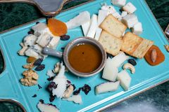 Cheese plate with several types of cheese, a bowl with honey in the middle, cookies, black raisins, dried apricots and walnuts. stock images