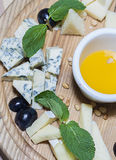 Cheese plate. Slices of different cheeses on a wooden board Royalty Free Stock Photos