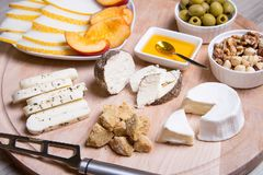 Cheese plate. 4 types of cheese, melon, nectarine, nuts, olives. Close-up. Selective focus stock images