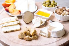 Cheese plate. 4 types of cheese, melon, nectarine, nuts, olives. Close-up. Selective focus stock photography