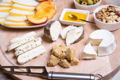 Cheese plate. 4 types of cheese, melon, nectarine, nuts, olives. Close-up. Selective focus royalty free stock image