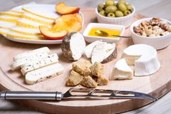 Cheese plate. 4 types of cheese, melon, nectarine, nuts, olives. Close-up. Selective focus royalty free stock photography