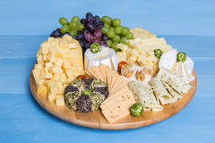 Cheese plate variation on a wooden blue table Royalty Free Stock Photography