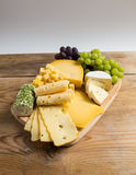 Cheese plate variation on a wooden table Stock Photography