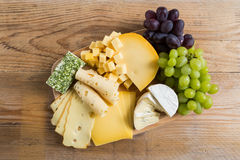 Cheese plate variation on a wooden table Royalty Free Stock Photo