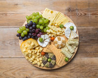 Cheese plate variation on a wooden table Royalty Free Stock Images