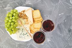 Cheese plate variety, and wine in glasses. On grunge grey background . Italian antipasti wine snacks set. Flat lay. Copy space stock photos