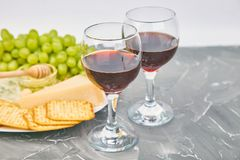 Cheese plate variety, and wine in glasses. On grunge grey background . Italian antipasti wine snacks set. Copy space stock photography