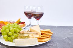 Cheese plate variety, and wine in glasses. On grunge grey background . Italian antipasti wine snacks set. Copy space stock images