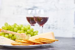 Cheese plate variety, and wine in glasses. On grunge grey background . Italian antipasti wine snacks set. Copy space stock photo