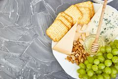 Cheese plate variety, and wine in glasses. On grunge grey background . Italian antipasti wine snacks set. Flat lay. Copy space royalty free stock photo