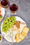 Cheese plate variety, and wine in glasses. On grunge grey background . Italian antipasti wine snacks set. Flat lay. Copy space royalty free stock photography