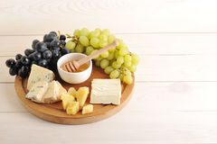 Cheese plate - various types of cheese, grapes green and black,. Honey on a wooden Board royalty free stock images
