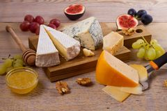 Cheese plate. Various types of cheese with grapes, honey, figs and nuts on rustic wooden table. Cheese plate. Various types of cheese with grapes, honey, figs royalty free stock images