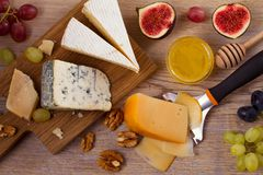 Cheese plate. Various types of cheese with grapes, honey, figs and nuts on rustic wooden table. View from above, top studio shot, horizontal royalty free stock photos