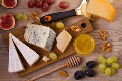 Cheese plate. Various types of cheese with grapes, honey, figs and nuts on rustic wooden table. View from above, top studio shot, horizontal stock photography