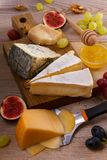 Cheese plate. Various types of cheese with grapes, honey, figs and nuts on rustic wooden table. Cheese plate. Various types of cheese with grapes, honey, figs stock images