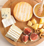 Cheese plate - various types of cheese, honey and figs Royalty Free Stock Image