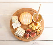 Cheese plate - various types of cheese, honey and figs Royalty Free Stock Photography