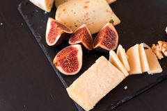cheese plate - various types of cheeses and figs and grapes royalty free stock photos