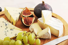 Cheese plate - various types of cheeses and figs and grapes on a Stock Photo