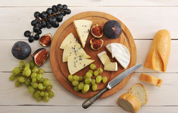 Cheese plate - various types of cheeses and figs and grapes on a Royalty Free Stock Photography