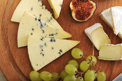Cheese plate - various types of cheeses and figs and grapes on a Royalty Free Stock Photo