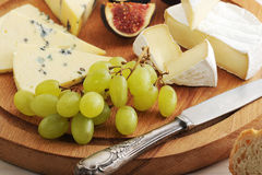 Cheese plate - various types of cheeses and figs and grapes on a Royalty Free Stock Images