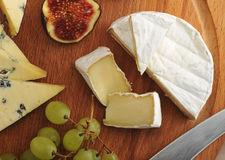 Cheese plate - various types of cheeses and figs and grapes on a Stock Photos