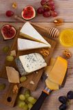 Cheese plate. Various types of cheese with grapes, honey, figs and nuts on rustic wooden table. View from above, top studio shot, vertical stock photos