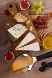 Cheese plate. Various types of cheese with grapes, honey, figs and nuts on rustic wooden table. View from above, top studio shot, vertical stock images