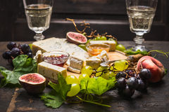 Cheese plate with white and dark grapes on a branch Peaches glasses on wooden rustic background. Cheese plate with white and dark grapes on branch Peaches stock images