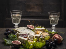 Cheese plate with white and dark grapes on a branch Peaches glasses on wooden rustic background Stock Image