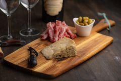 Cheese plate with wine in the background on a dark wood table. With some olives royalty free stock photography