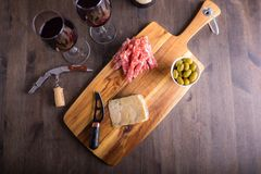 Cheese plate with wine in the background on a dark wood table. And some olives and a cork stock photos