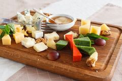 Cheese plates served with grapes, jam and nuts. Wooden desk stock image