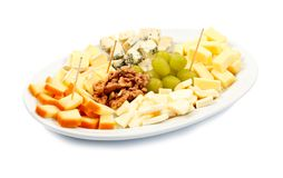 Cheese platter. Rich cheese platter with nuts and grape Royalty Free Stock Images
