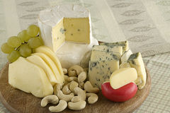 Cheese platter. Cheese snaks and nuts on a wood platter Royalty Free Stock Images