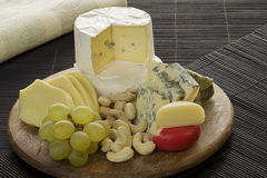Cheese platter. Cheese variation and nuts on a wood platter Royalty Free Stock Photo