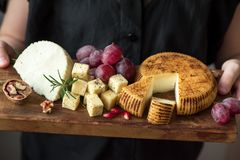 Cheese platter in hands of cheese maker. Cheese platter with assorted cheeses, grapes, nuts in hands of cheese maker. Italian cheese and fruit platter Stock Photography