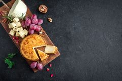 Cheese platter. With assorted cheeses, grapes, nuts over black background, copy space. Italian cheese and fruit platter, top view Royalty Free Stock Images