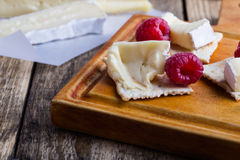 Brie cheese with fresh raspberries and crackers. Cheese platter. Brie soft cheese served with fresh raspberries and crackers on rustic wooden cutting board Stock Photos