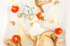 Cheese platter with cashew nuts. Overhead view of a cheese platter with cashew nuts and wedges of assorted hard cheeses, blue cheese and semi-soft cream cheese royalty free stock photos