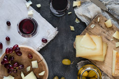 Cheese platter of chopped Spanish hard cheese manchego and sliced Italian pecorino toscano on wooden boards, with green olives royalty free stock image