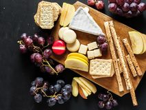 Cheese platter on cutting board with pieces of fresh apple and grains on a black chalkboard background stock photography